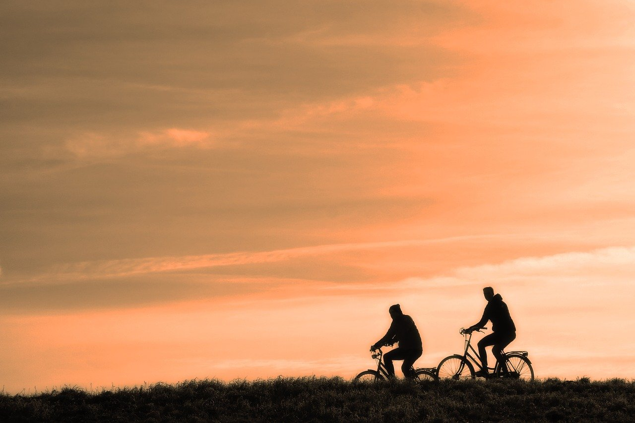 Ciclisti al tramonto   Foto di Foto di Mabel Amber su Pixabay